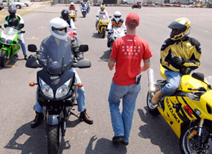 This is an image of an instructor and his students in a motorcylce safety course.